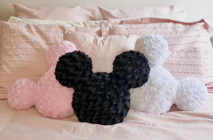 Mickey mouse head shaped pillows on a bed