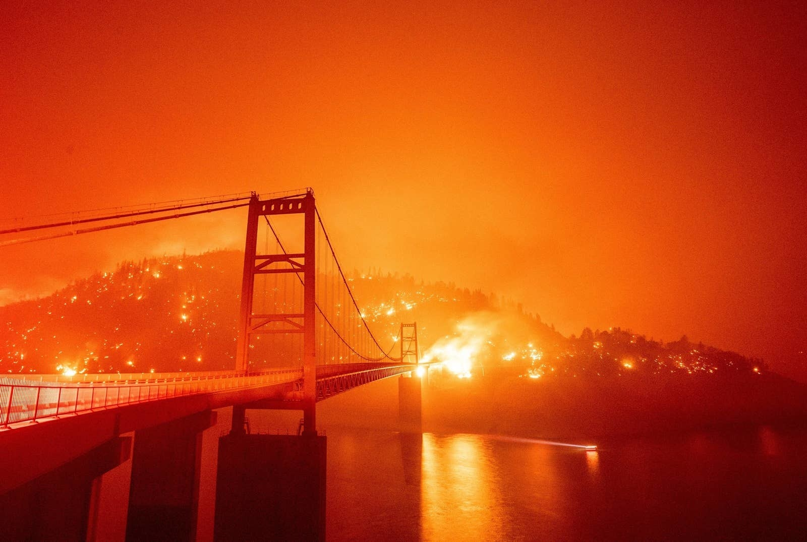 A flaming hillside with a bridge in the foreground, with a bright orange sky