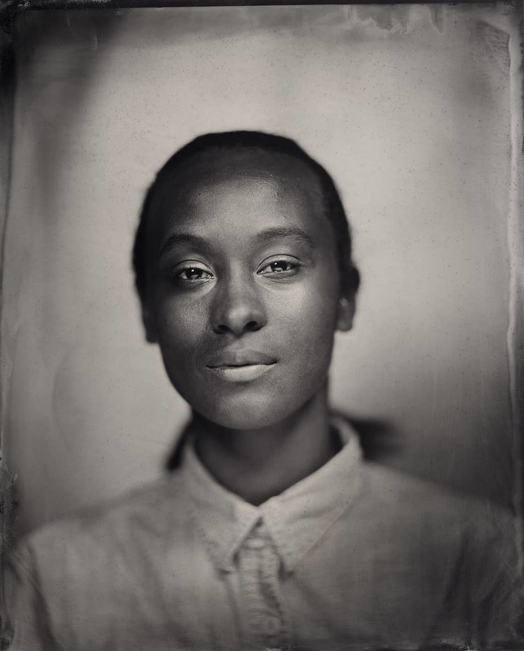 A young girl staring into the camera in a tintype image