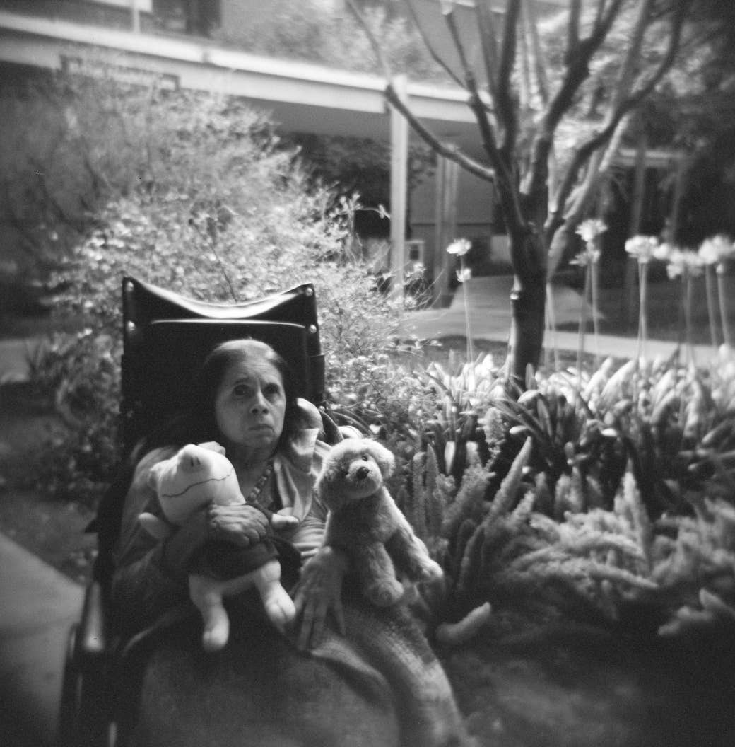 An older woman sits in a wheelchair with two stuffed animals