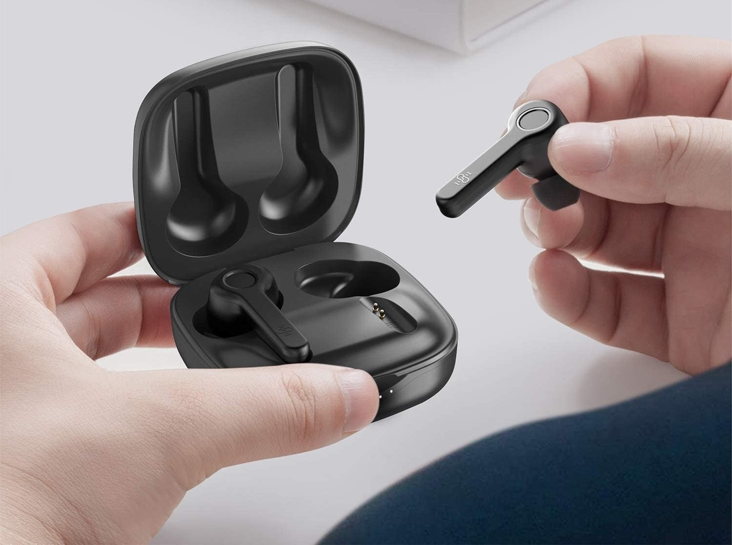 person taking an earbud out of the charging case