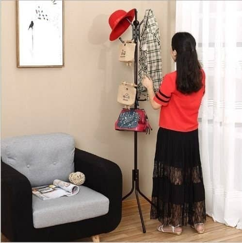 A person hanging clothes on the rack.