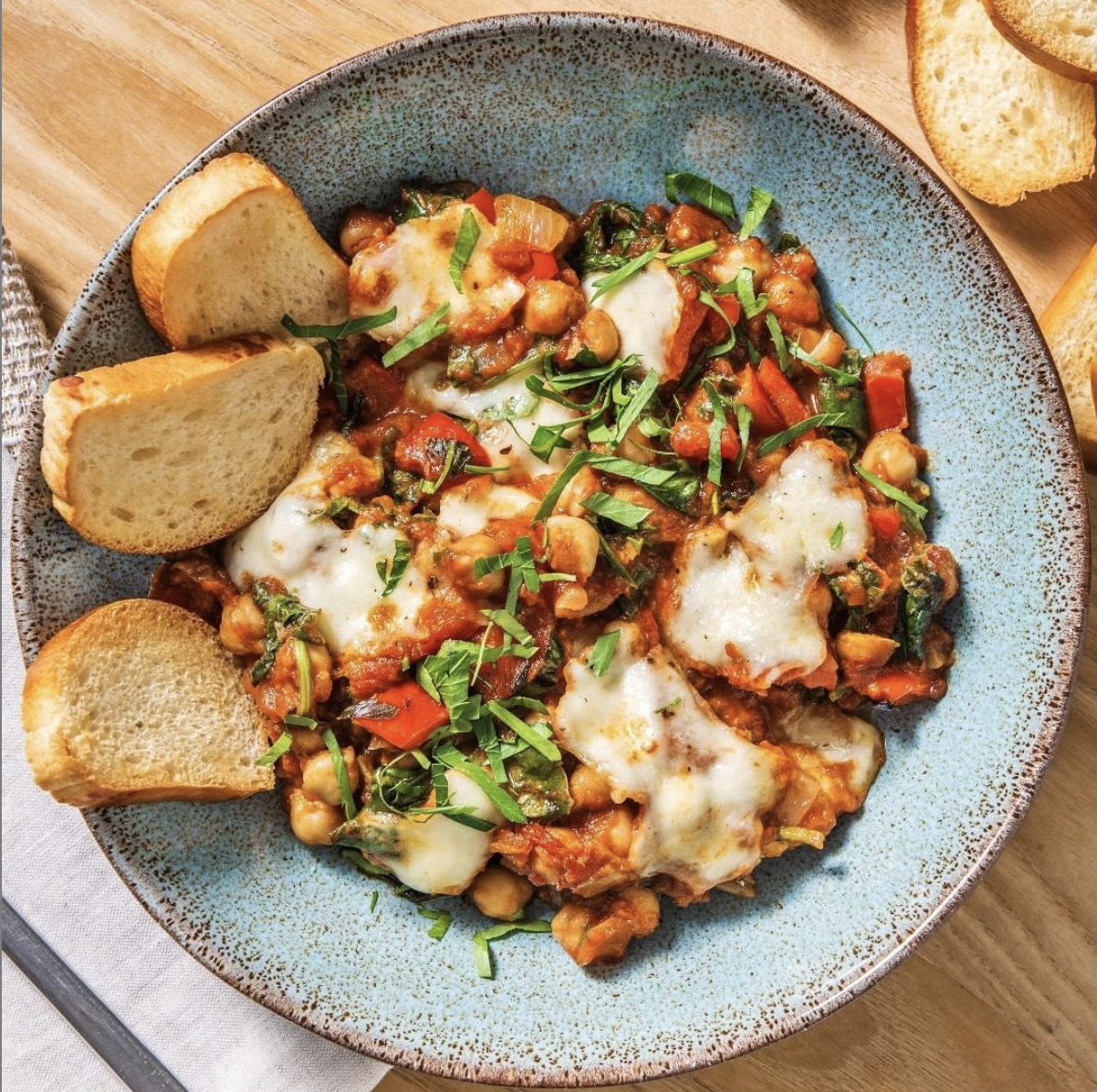 shakshuka in a bowl with bread on the side
