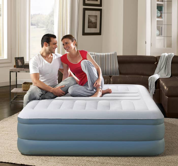 two people sitting on an air mattress in a living room