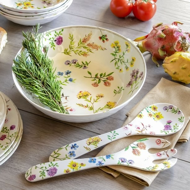 floral serving bowl and serving forks and spoon with a rosemary sprig