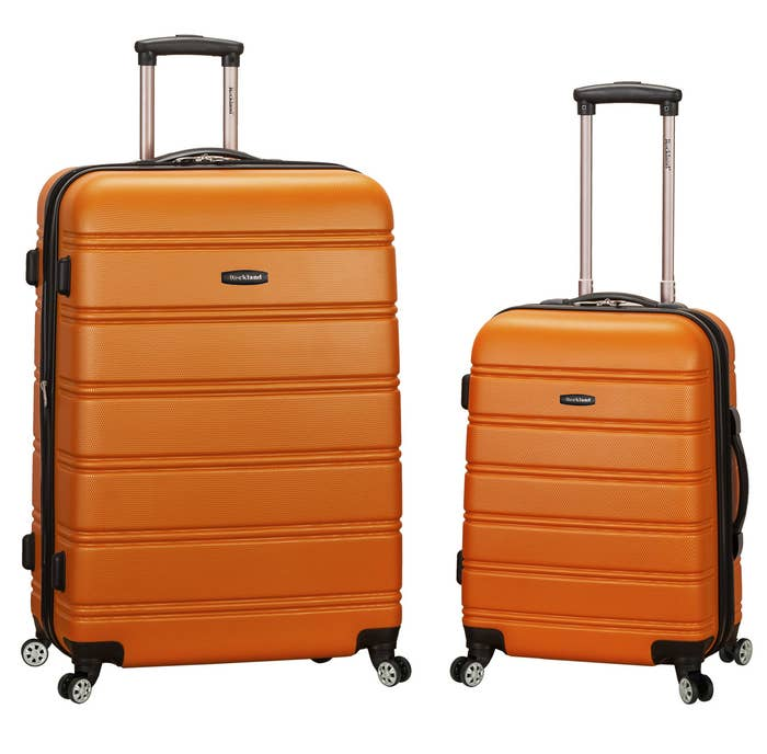 two orange hard-shell suitcases with 360-degree spinner wheels