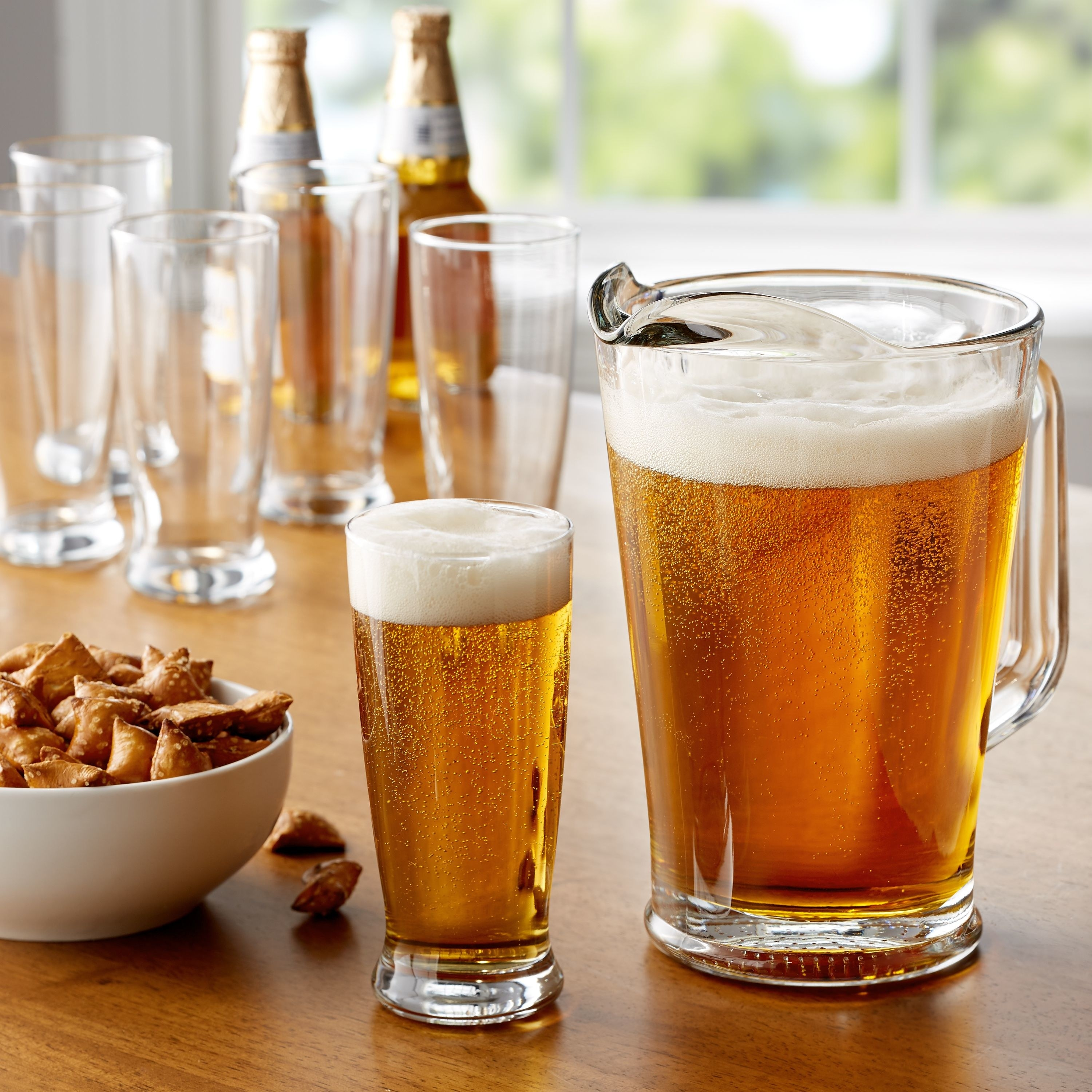 big pitcher and pint glasses with beer in them on a wood table