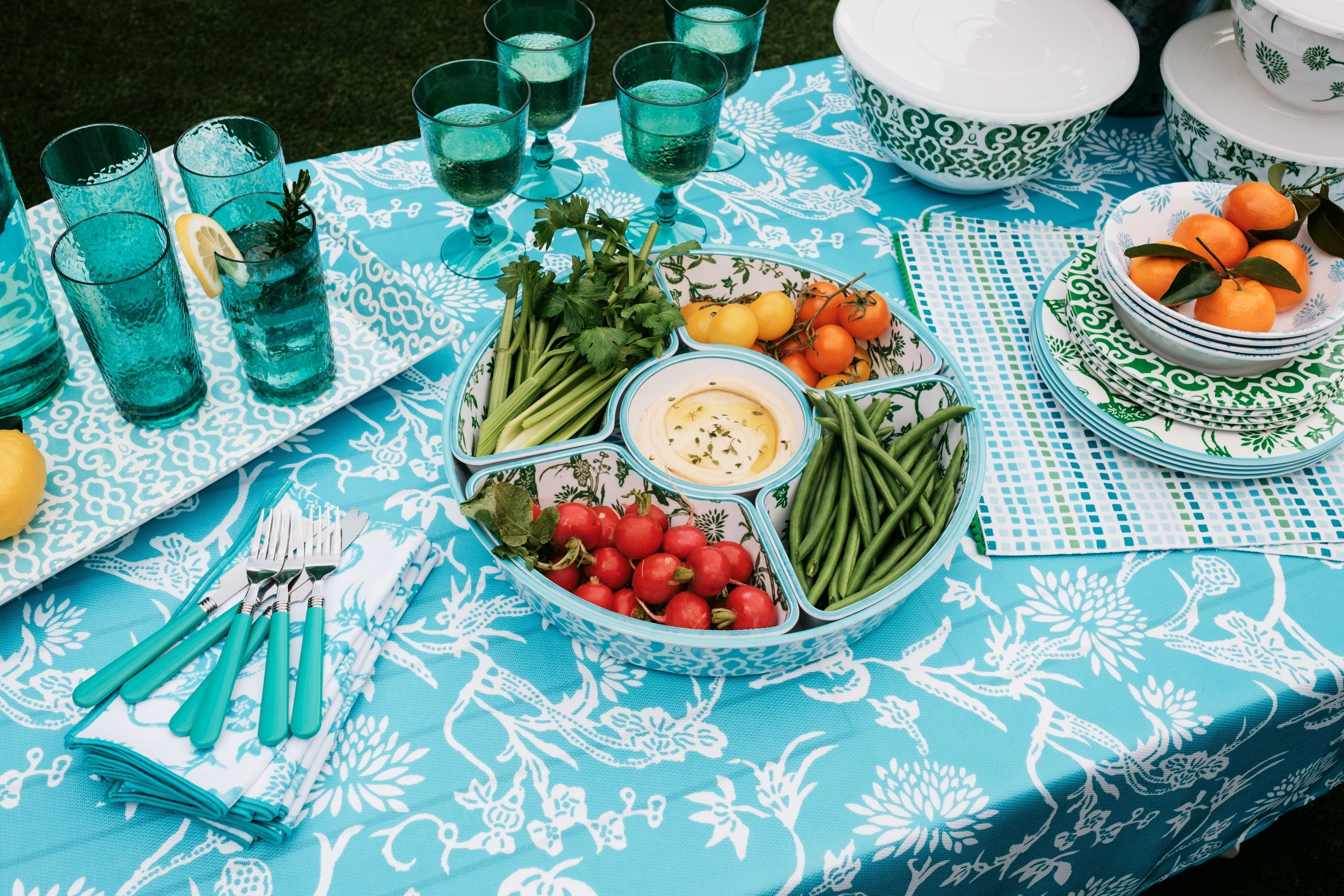 picnic table with a chip and dip server holding hummus and vegetables