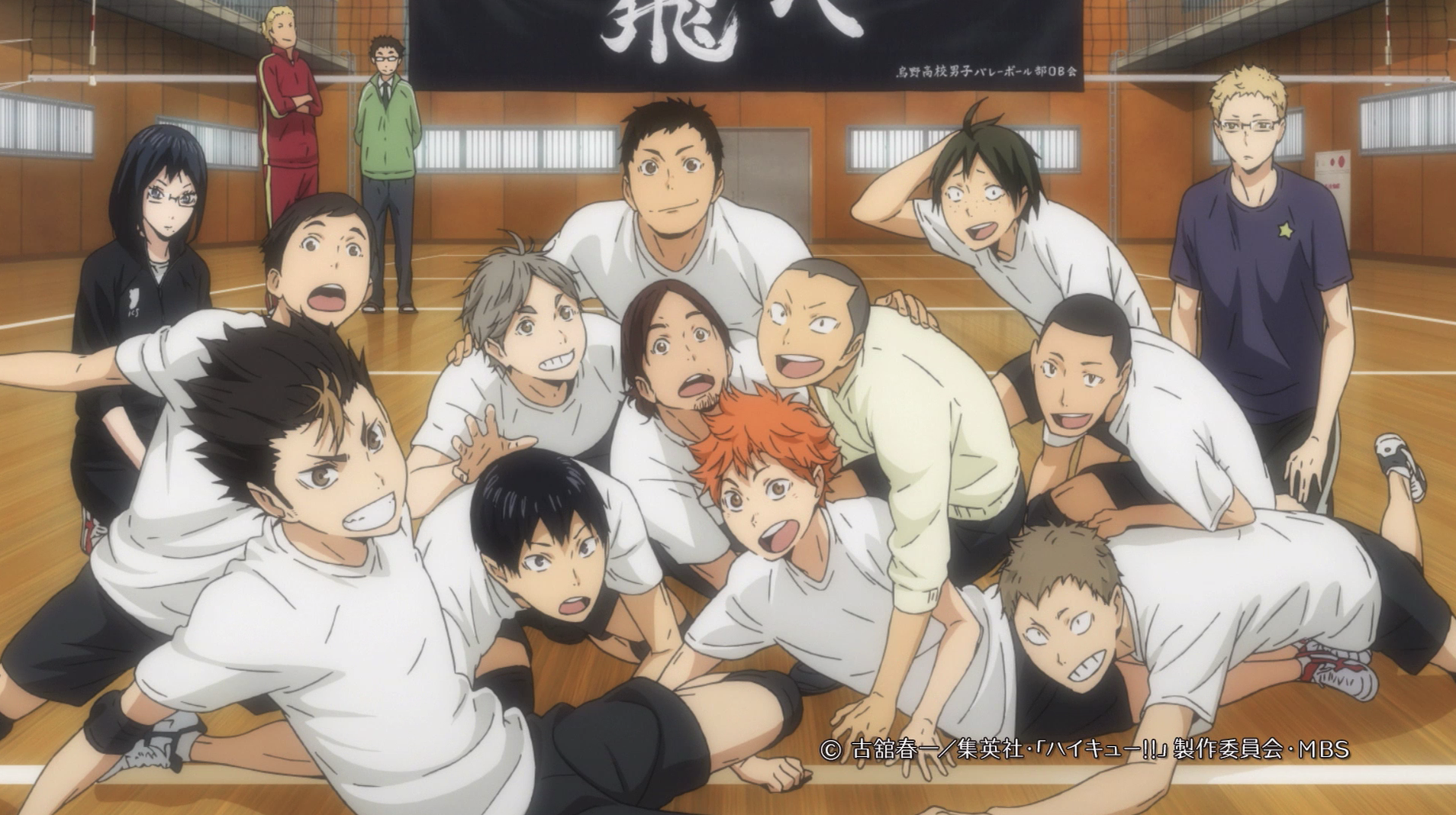 Karasuno's volleyball team huddling together on the floor while in the gym