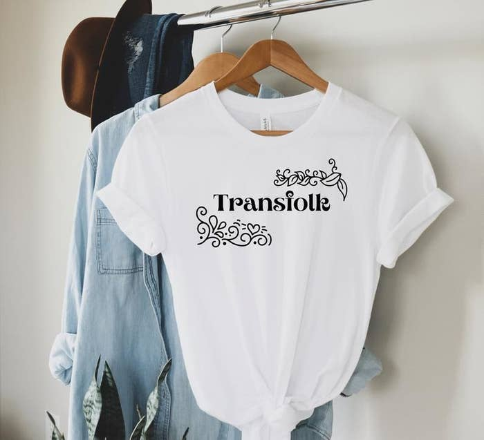 """a white t-shirt that says """"transfolk"""" in the center in black lettering with hearts and leaves around the words"""