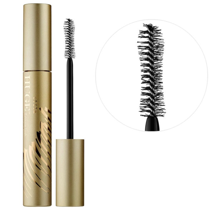 The gold tube of mascara with a close-up of the plush applicator wand