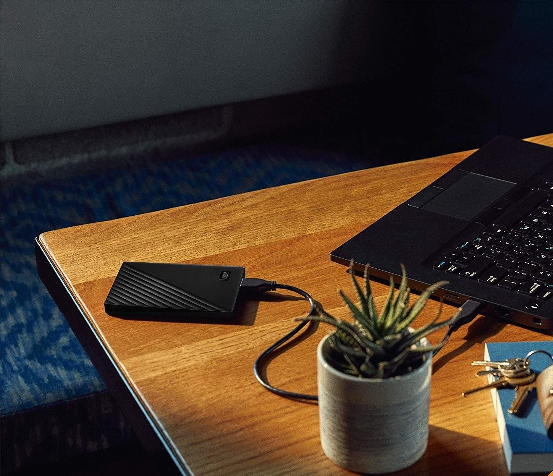 A small rectangular external hard drive lying next to a laptop