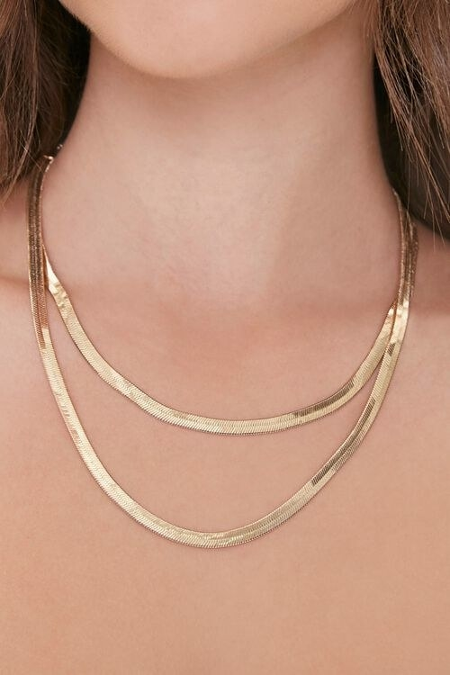 a model wearing the two flat gold necklaces