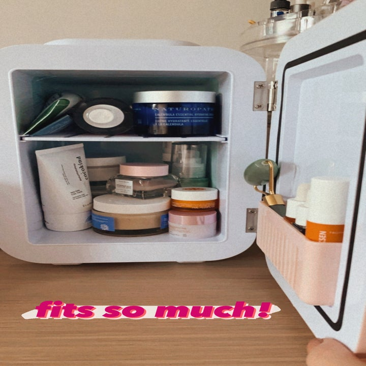 """The fridge open to show two shelves, door storage and text """"fits so much!"""""""
