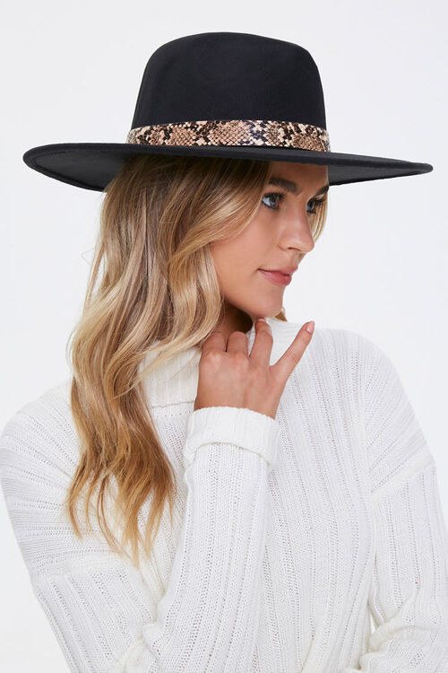 a model in a black wide brim hat with faux snakeskin trim