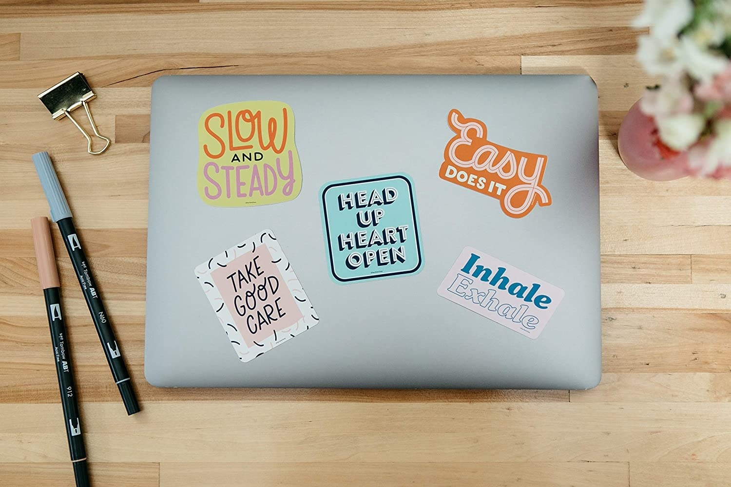 "A laptop with the stickers that read ""head up heart open,"" ""inhale exhale,"" ""easy does it,"" ""slow and steady,"" and ""take good care"" in cute fonts"