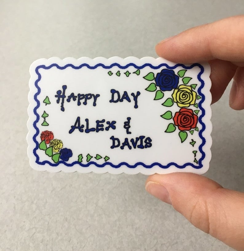 "A sticker shaped like the ""Happy Day Alex & Davis"" cake from the show"