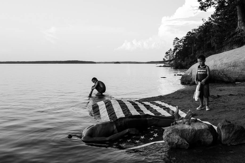 A man lying on a US flag at the edge of a lake with his head underwater with two young boys looking on
