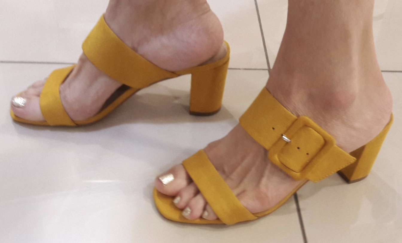 Reviewer wearing the slip-on block heel sandals with two straps across the top where one has a thick buckle in mustard yellow