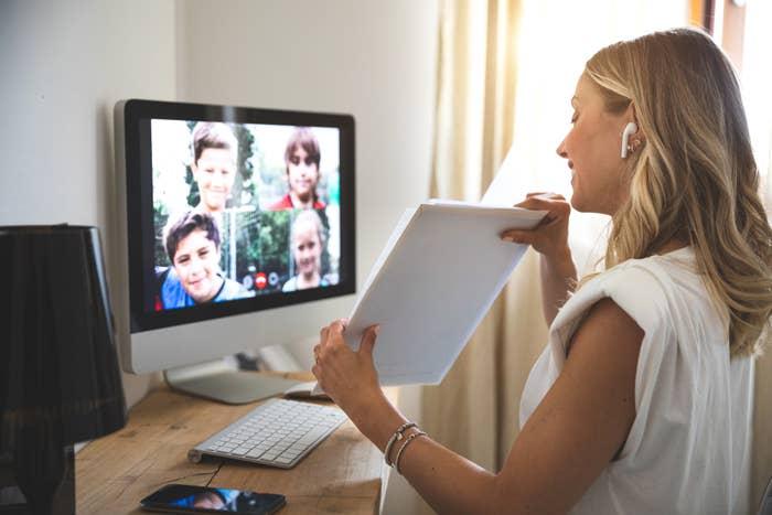 A teacher virtually teaches young students on a video call