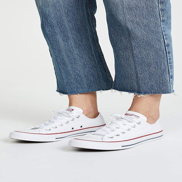 Front view of a model wearing the white sneakers
