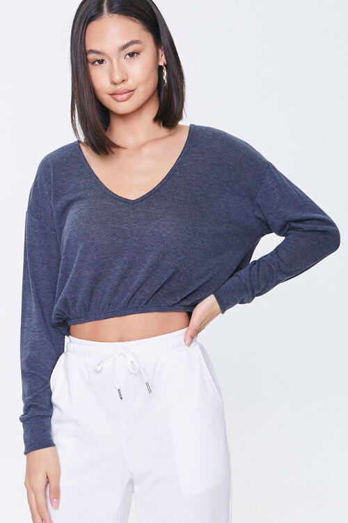 a model in a cropped navy top with long sleeves
