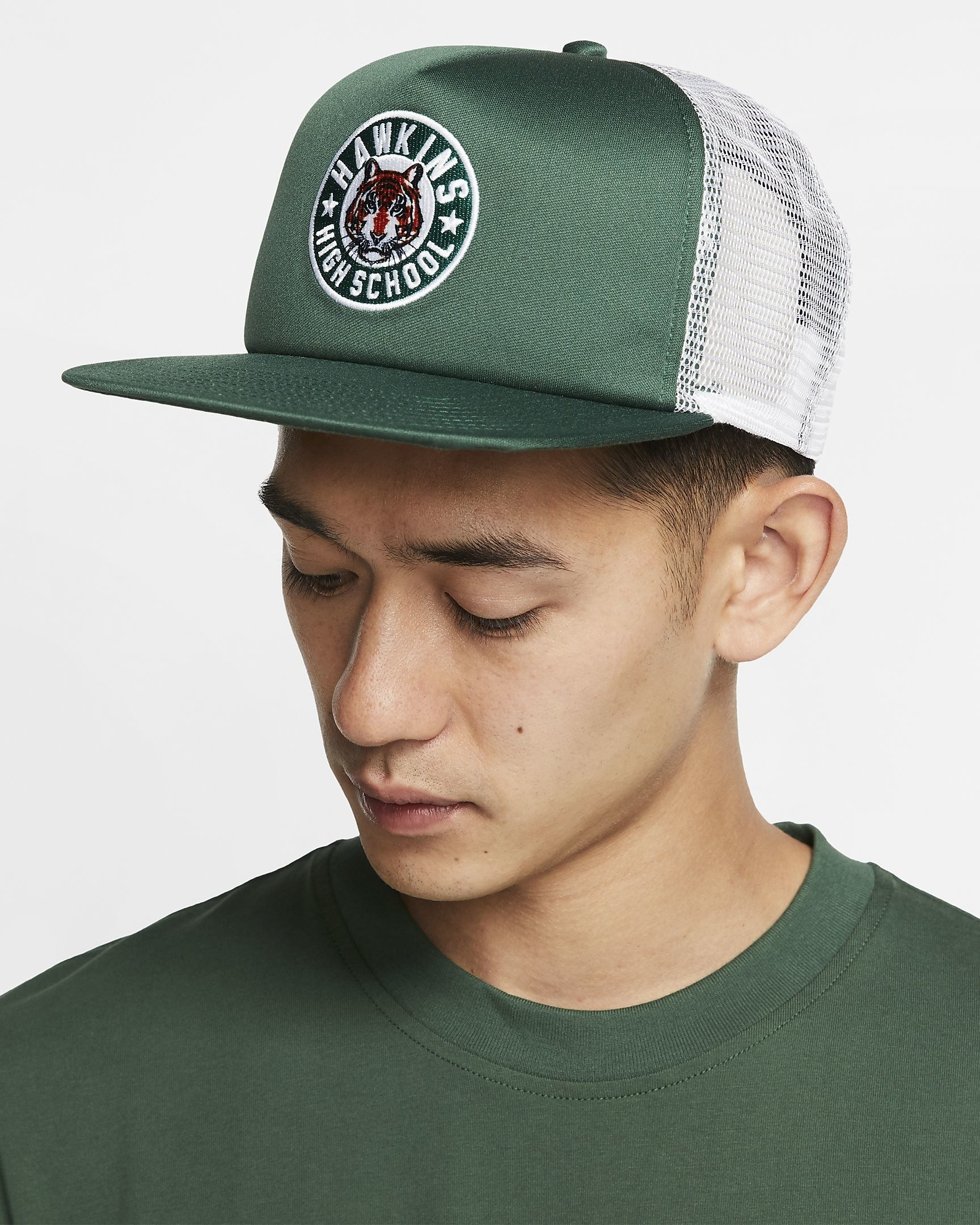 A model wearing the green and white mesh back baseball cap with the Hawkins Middle School tiger logo