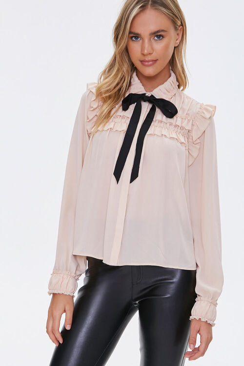a model wearing the top in pink with ruffles on the cuffs and the top half of the shirt