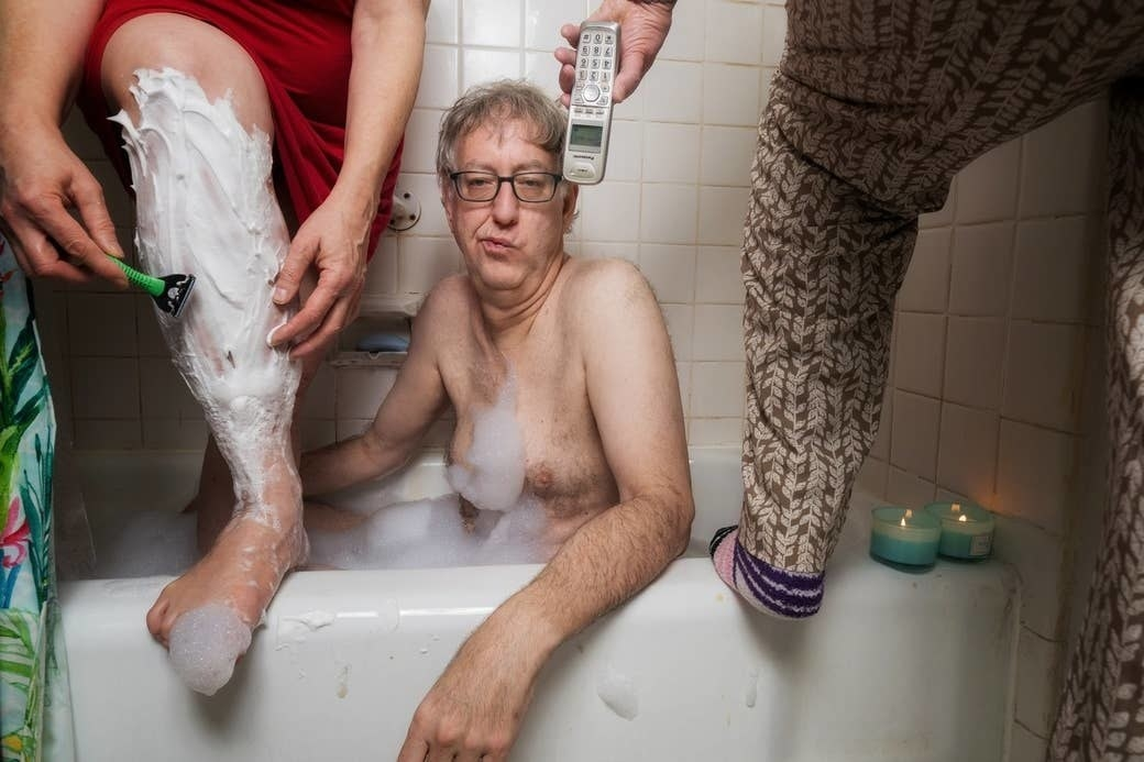 A man in a tub with two women on either side of him shaving their legs and handing him the phone