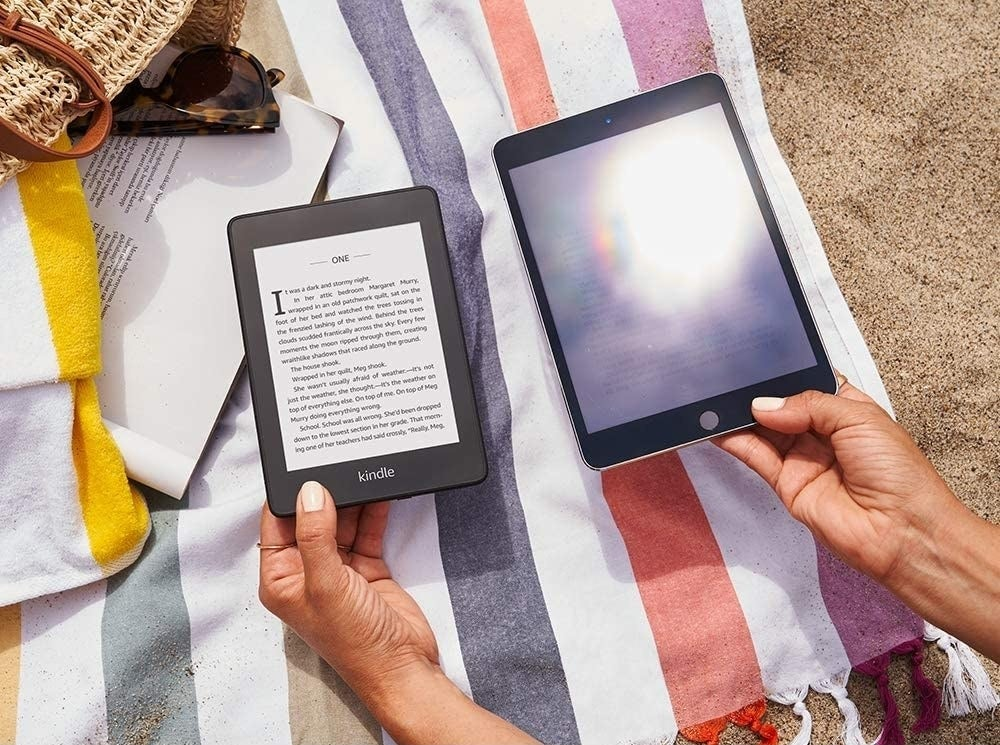 person holding the kindle next to another tablet to show that the tablet has glare
