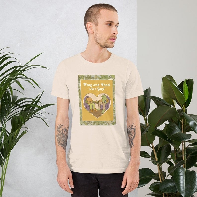 """a model wearing the tan shirt that reads """"Frog and Toad are gay"""" with a heart-shaped image of Frog and Toad in the center"""