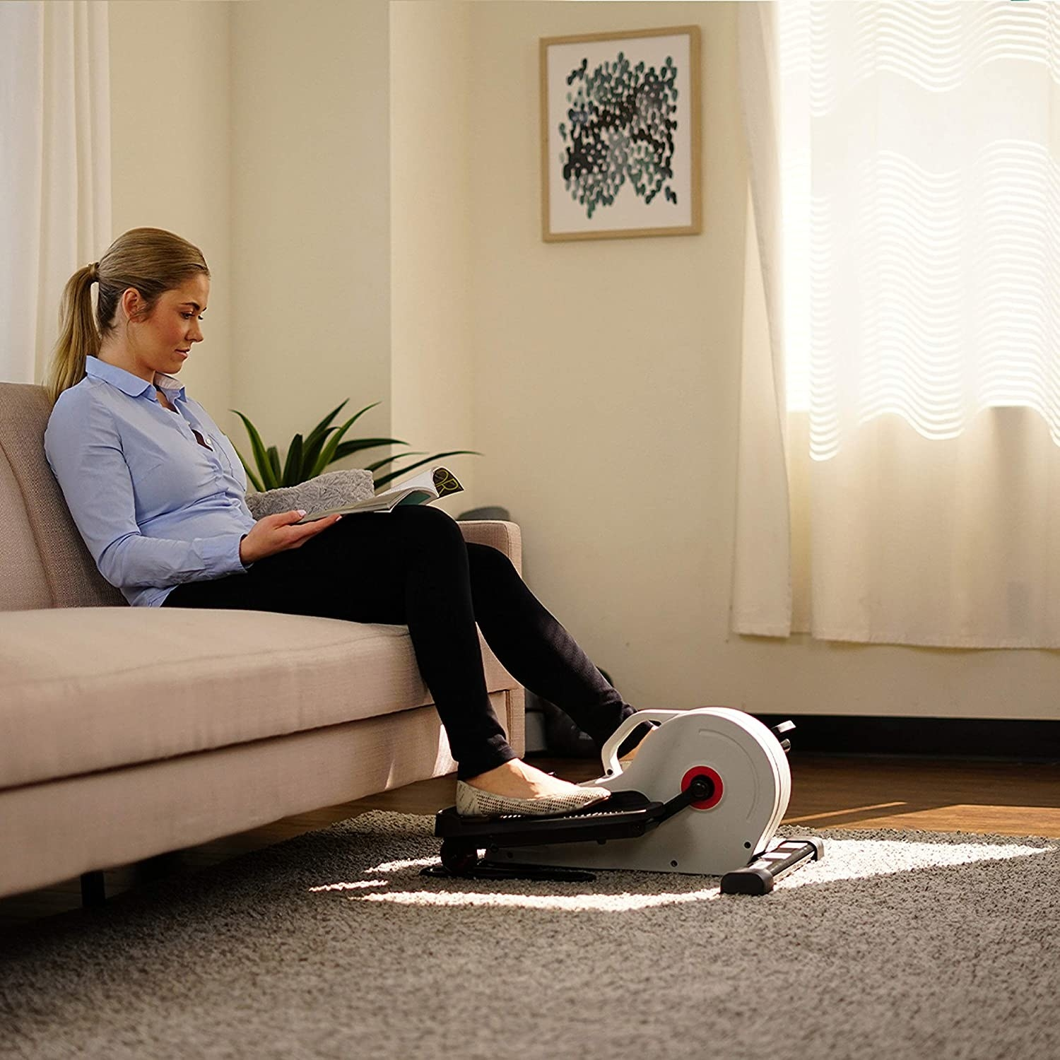 person using the elliptical while sitting on the couch