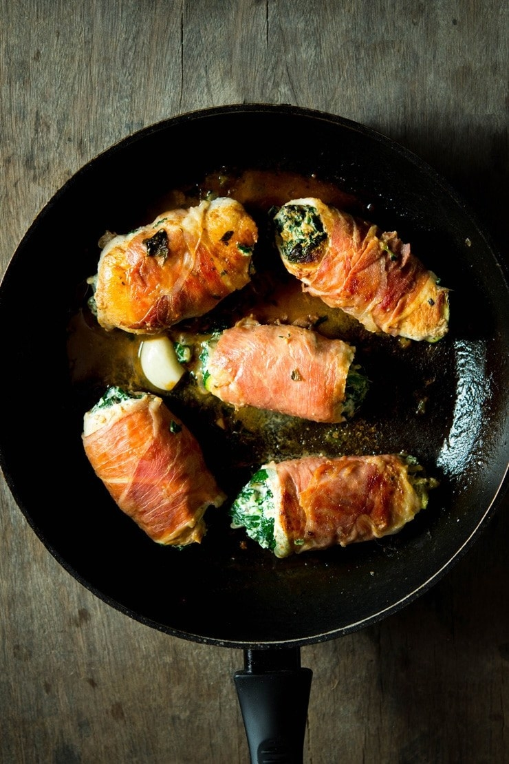 A skillet of five chicken breasts rolled with prosciutto, spinach, and ricotta cheese.