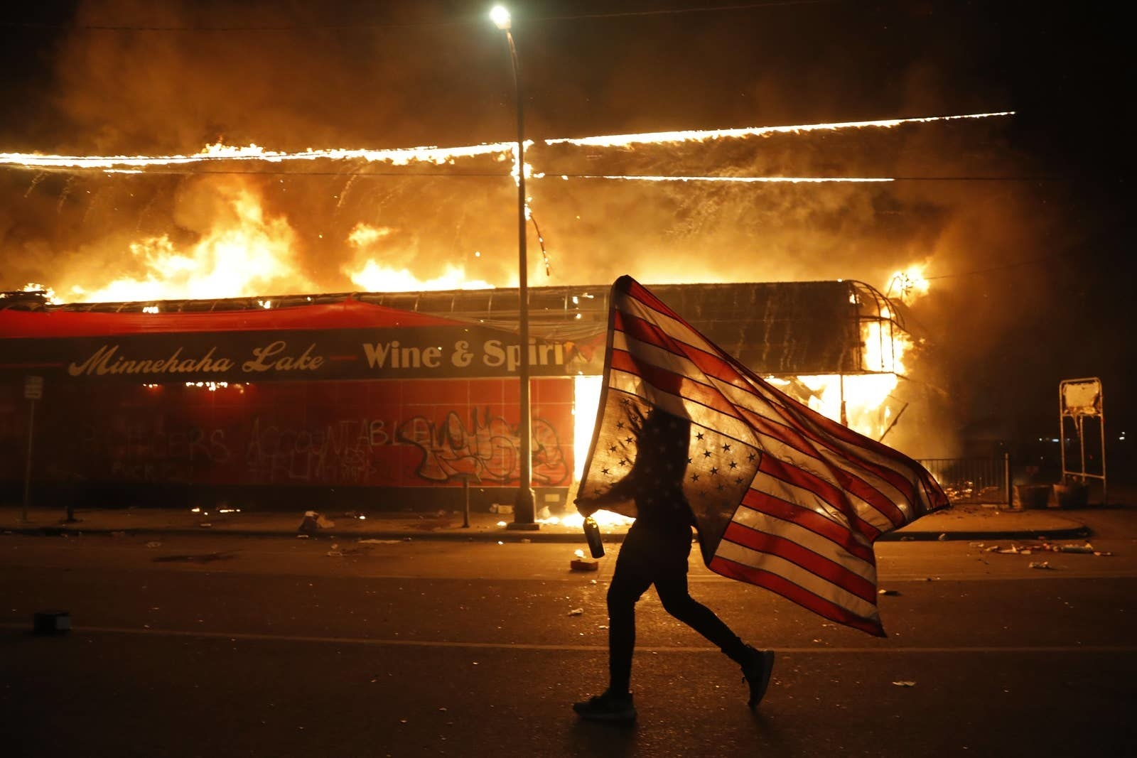 A man carrying an upside-down US flag walks by a burning liquor store at night
