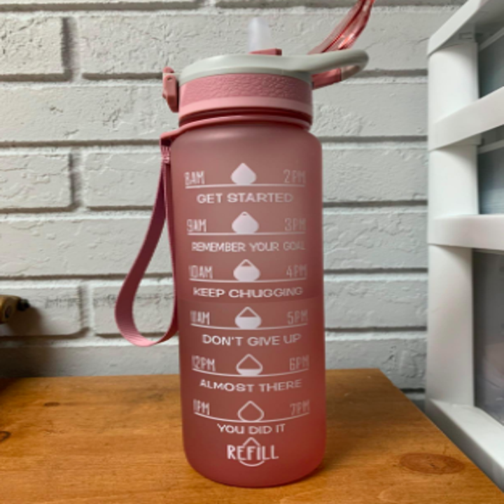 reviewer pic of pink water bottle with text on side encouraging you to drink more water