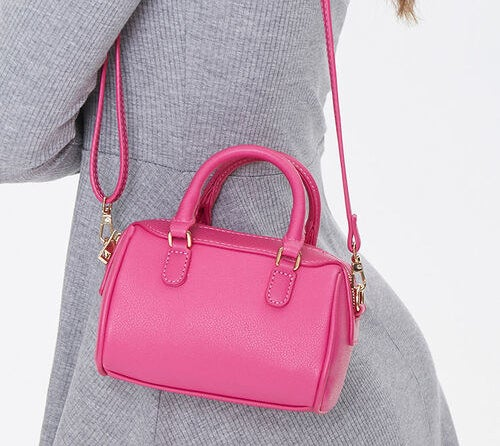 a model wearing a small hot pink bag
