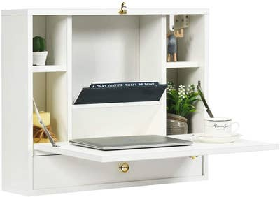 open white wall cabint with a fold-down desktop revealing a surface for a laptop, nooks for storage, and a drawer below the desktop surface