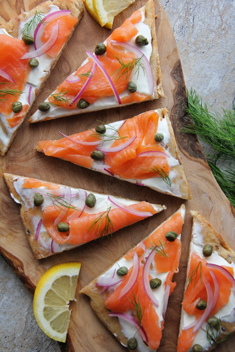 A flatbread topped with cream cheese, smoked salmon, capers, and red onion.