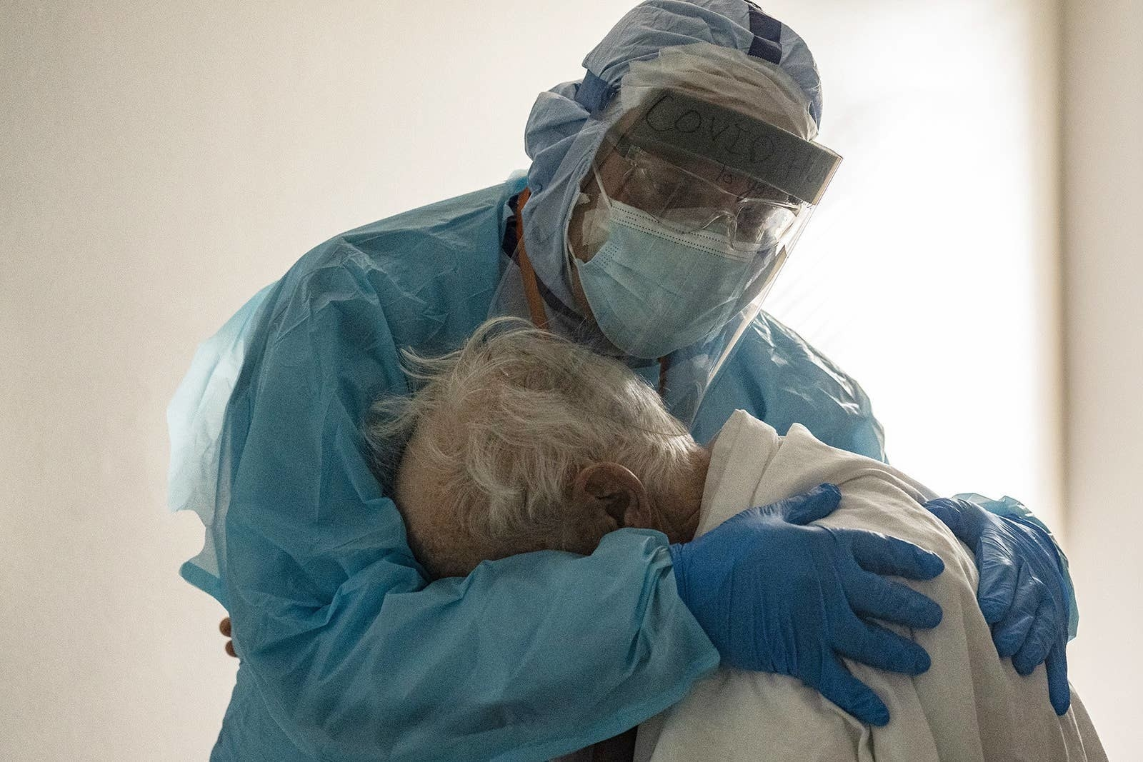 A doctor in full protective gear hugging a patient