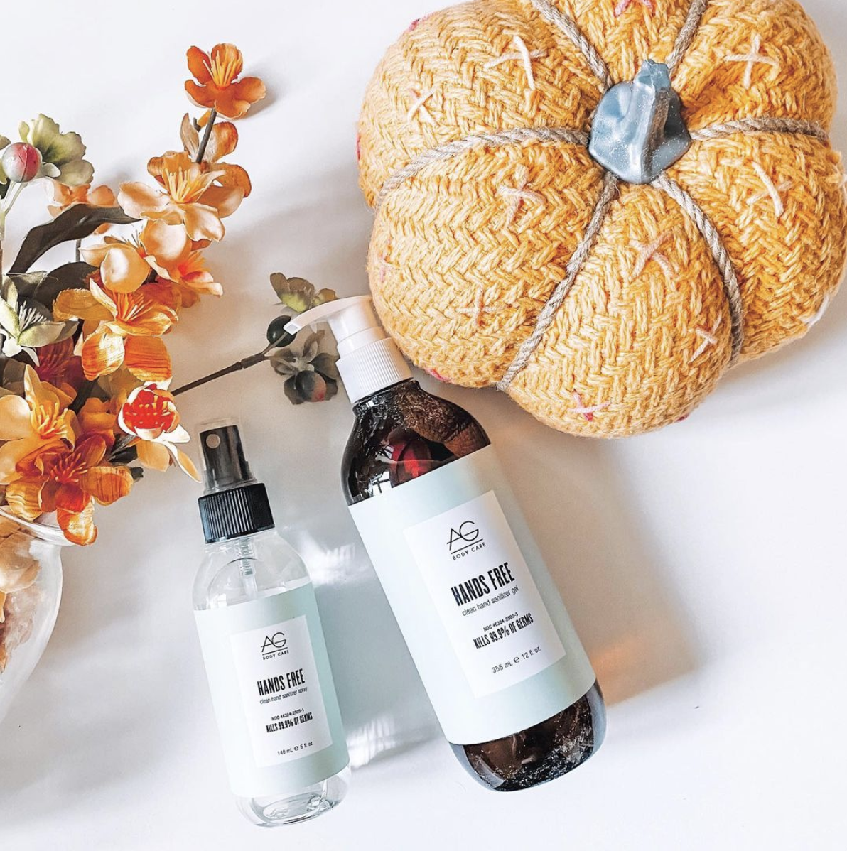 Two AG Hair products next to a knit pumpkin and flowers