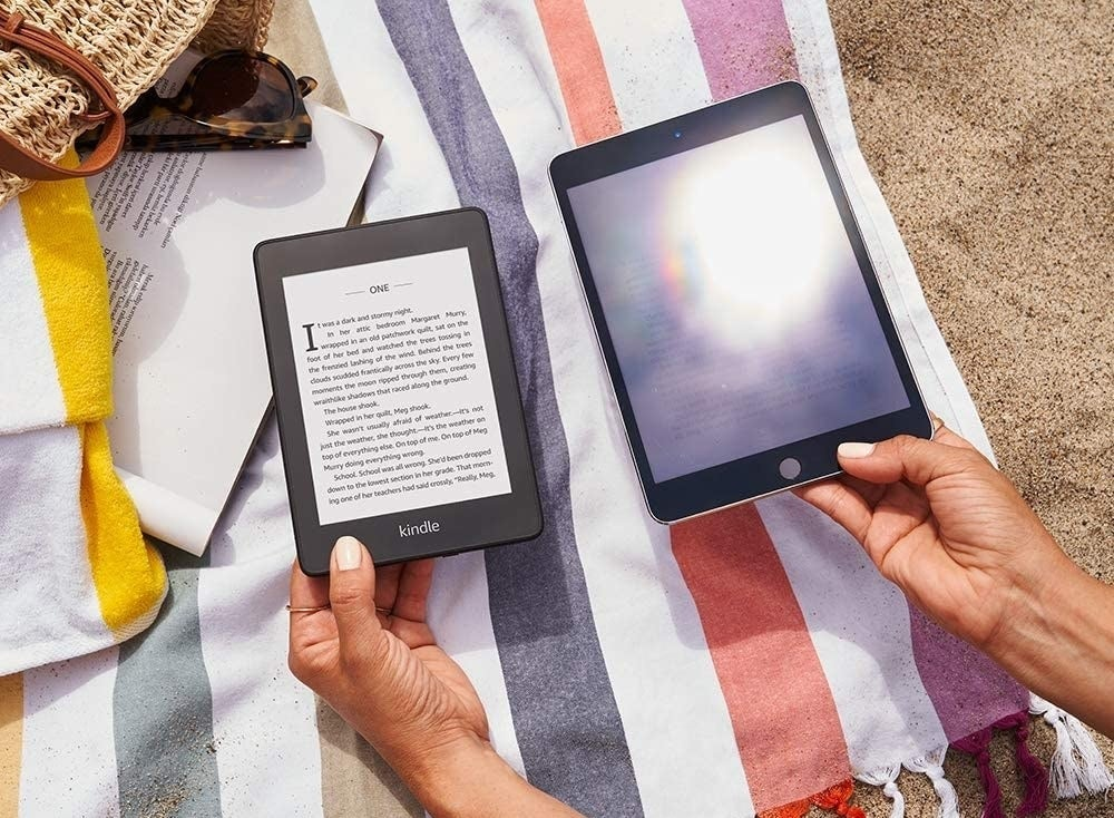 A person holding up the Kindle paperwhite next to a glaring tablet