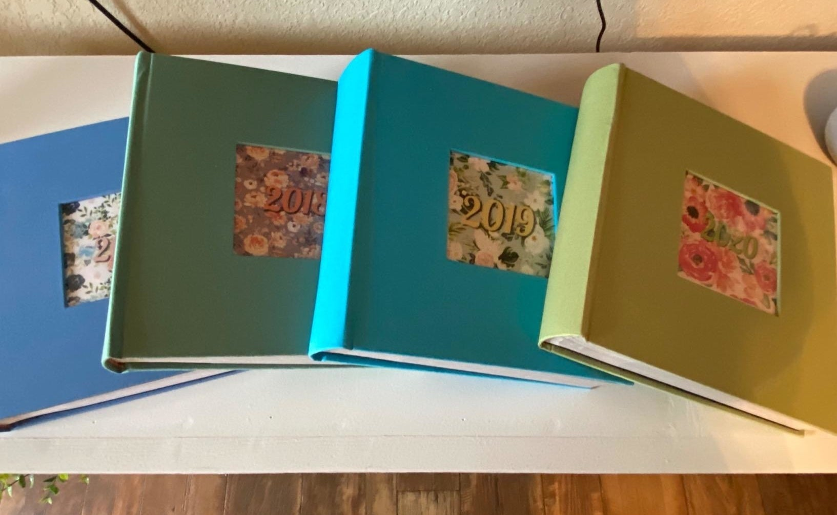 reviewer's four photo albums in different colors, marked with the year
