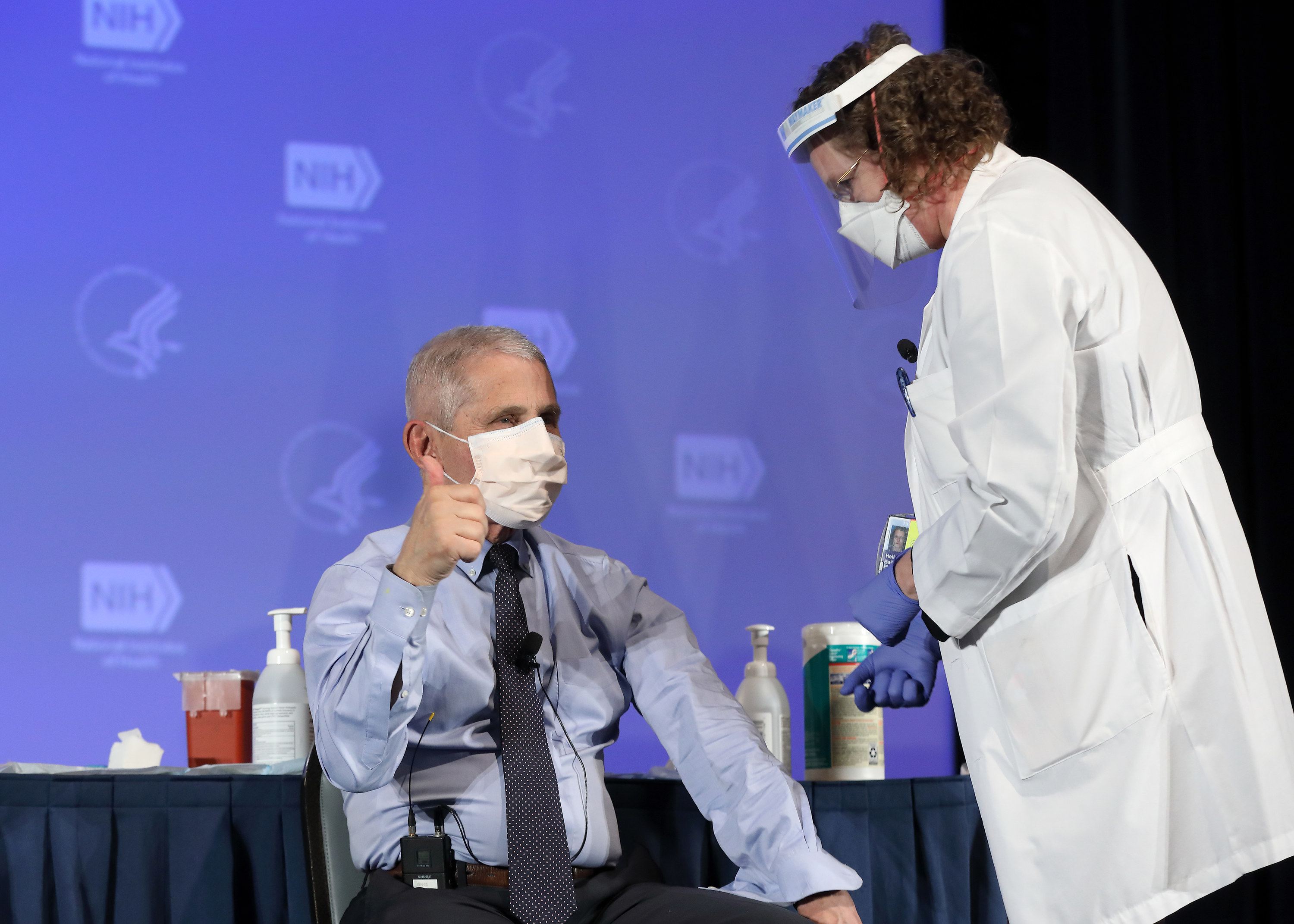 Dr Anthony Fauci gives a thumbs-up, wearing a face mask and about to receive a vaccine