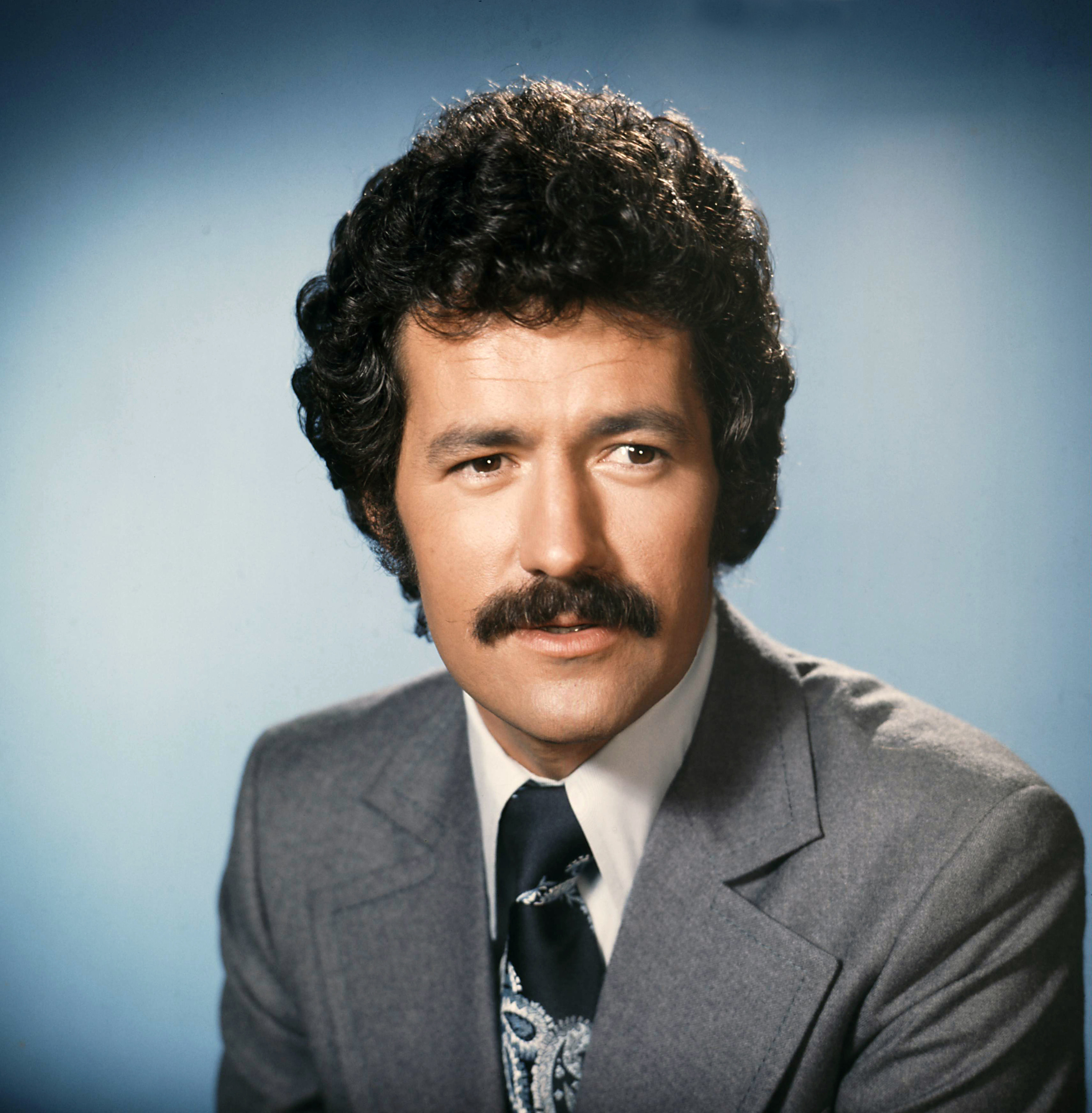 Trebek on blue background looking off to side of the camera
