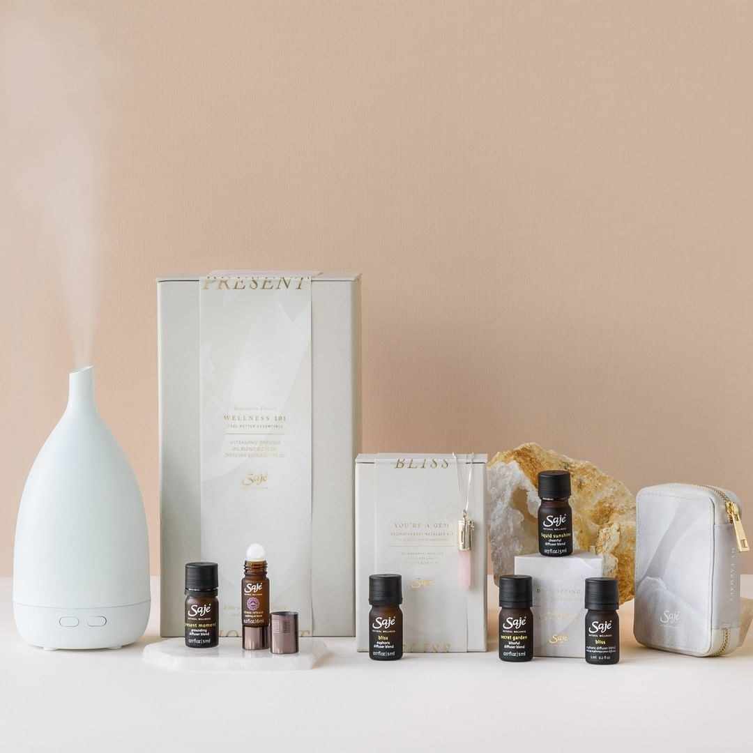 A diffuser next to several bottles of essential oils and rollerballs