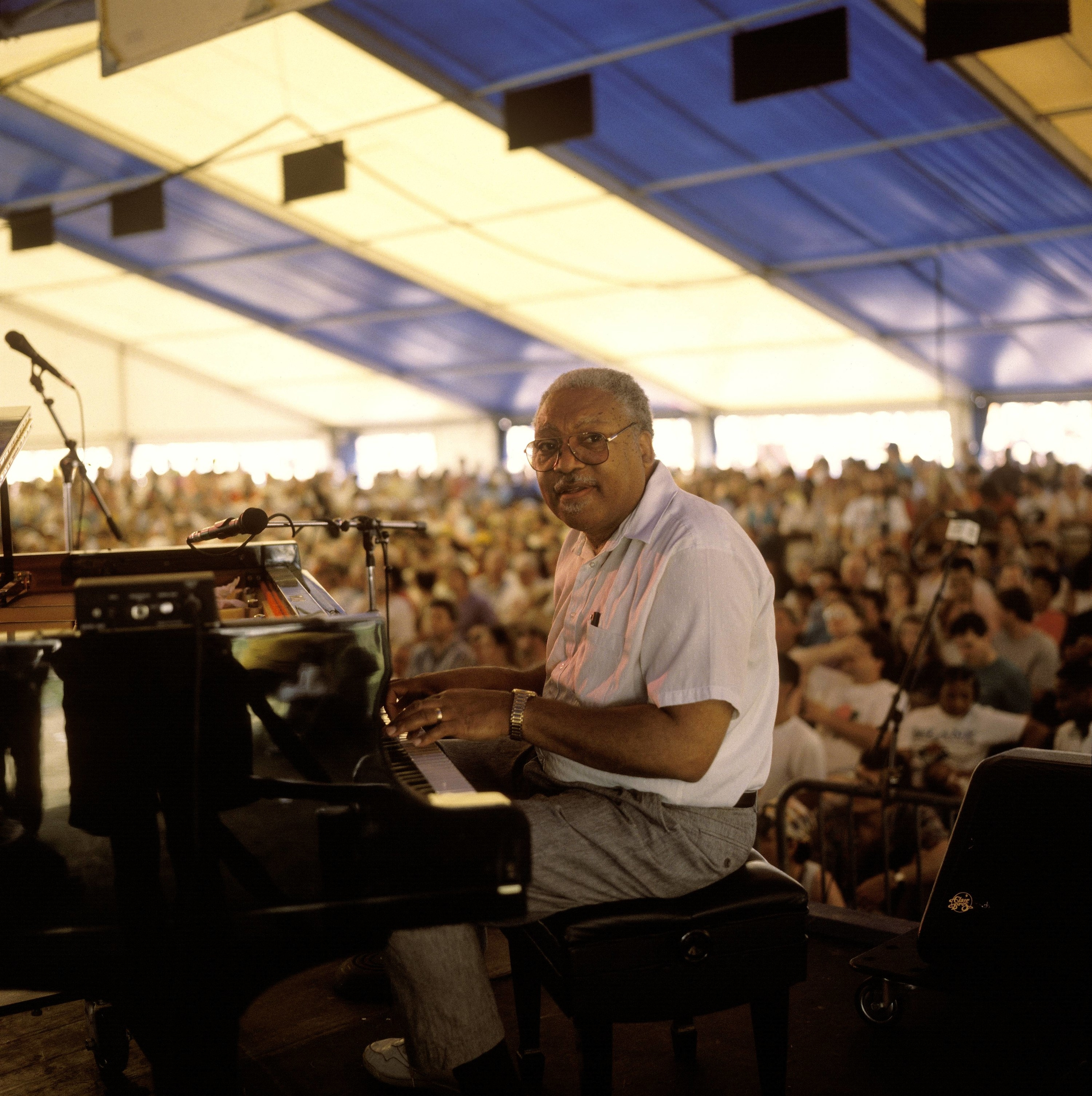 Man at a piano on stage with a crowd behind him