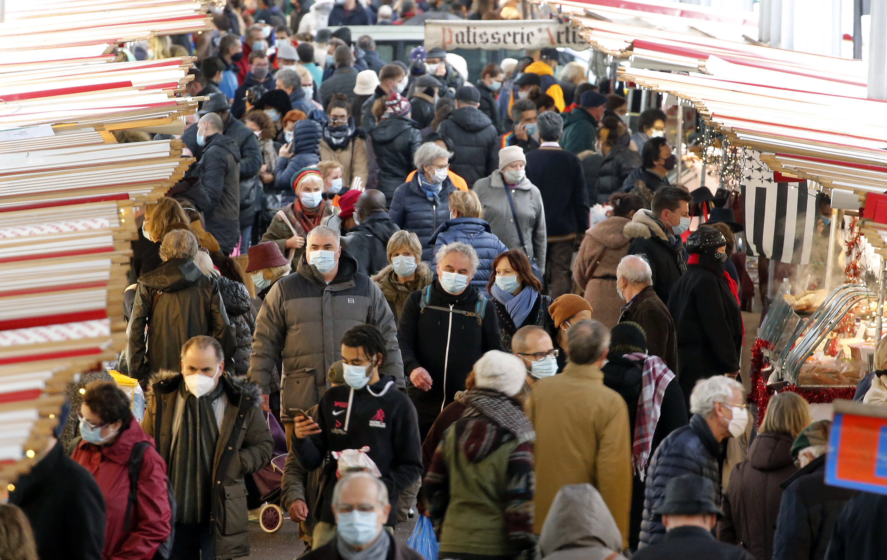 A crowd of people walk with face masks on
