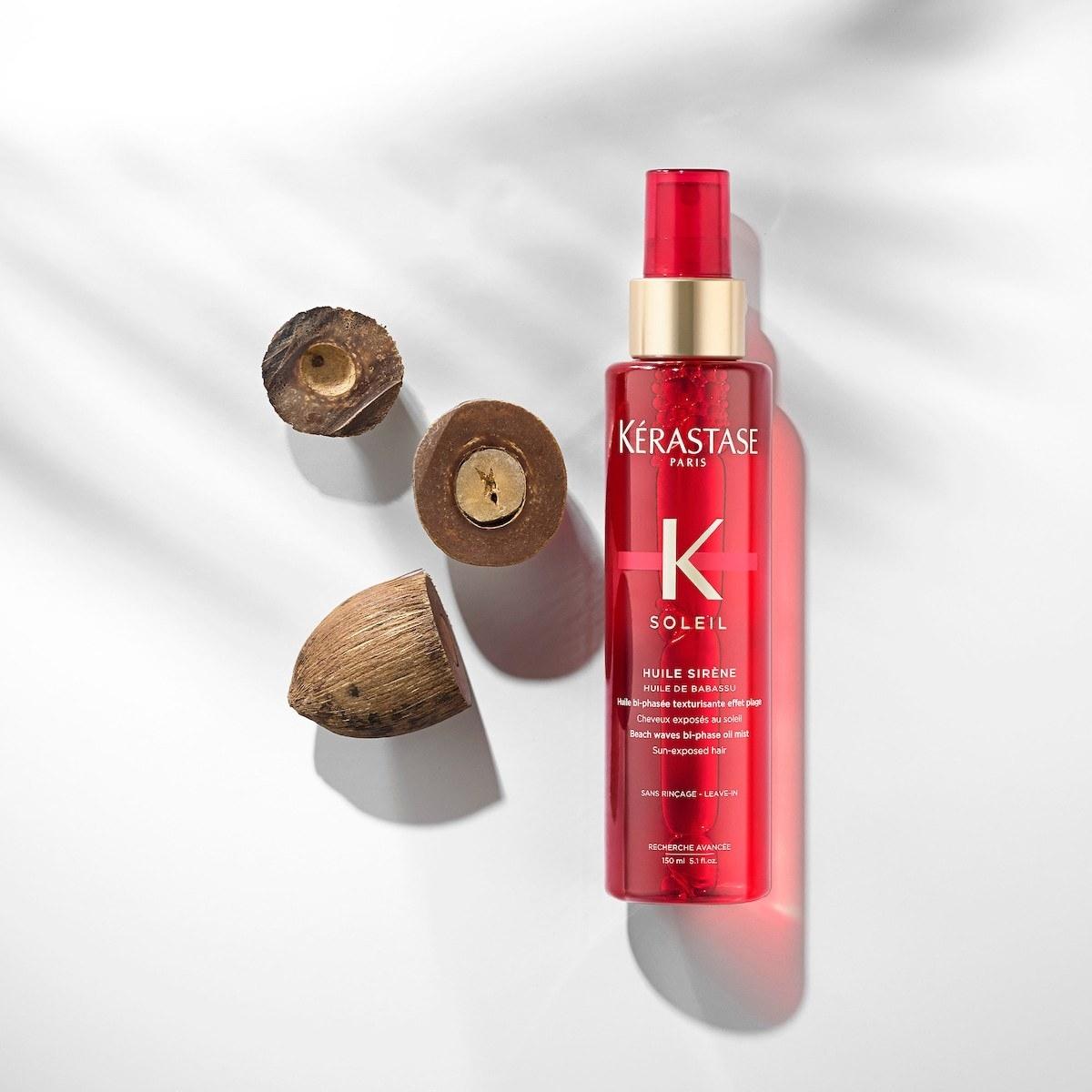 The red spray bottle next to a few babassu seeds