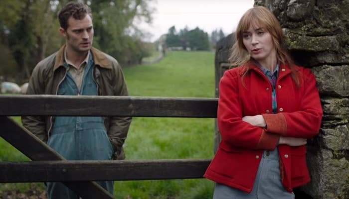 Wild Mountain Thyme still: Jamie Dornan stands behind a wooden fence and Emily Blunt stands in front of it