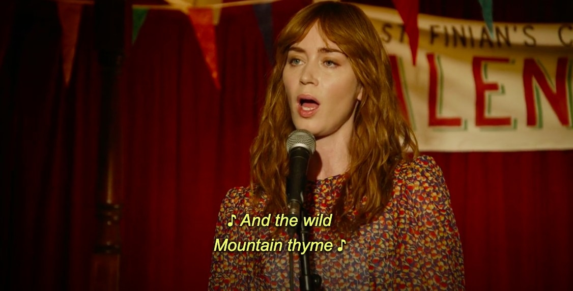 """Rosemary sings into a microphone, the caption reads """"And the wild mountain thyme"""""""